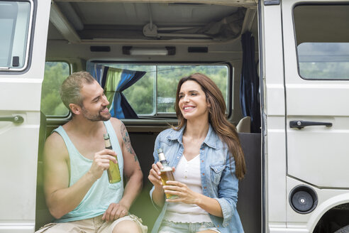 Smiling couple with beer bottles in a van - FMKF002802