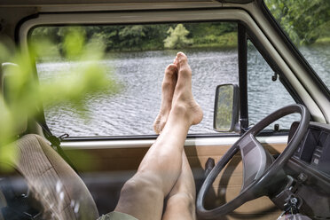 Legs of a man relaxing in a van at lakeside - FMKF002811