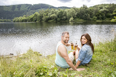 Smiling couple with beer bottles sitting at lakeside - FMKF002814
