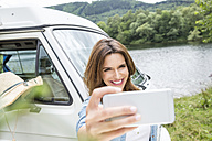 Smiling woman beside van at lakeside taking a selfie - FMKF002826