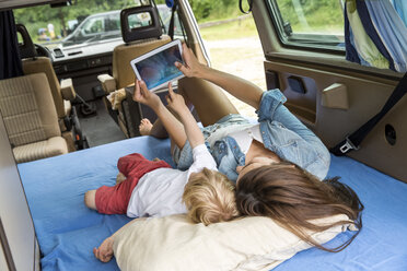 Mother and son lying on mattress in van using tablet - FMKF002838