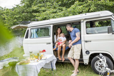 Happy family with van at lakeside - FMKF002844