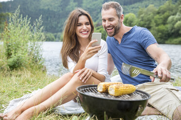 Happy couple with cell phone having a barbecue at lakeside - FMKF002847