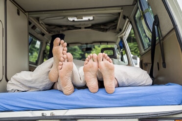 Feet of a couple lying on mattress in van - FMKF002856