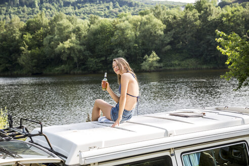 Young woman sitting on roof of a van at lakeside drinking a beer - FMKF002859