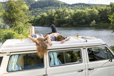 Young couple lying on roof of a van at lakeside - FMKF002862