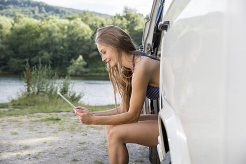 Young woman sitting in a van at lakeside using digital tablet - FMKF002865