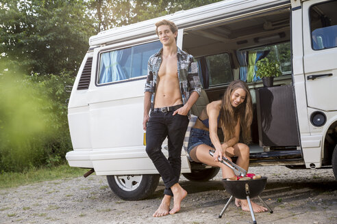 Young couple having a barbecue at a van - FMKF002868