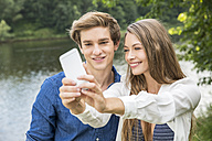 Young couple at lakeside taking a selfie - FMKF002874