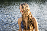 Laughing young woman in a lake - FMKF002877