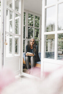 Smiling woman with book sitting on lounge in her winter garden - KNSF000247