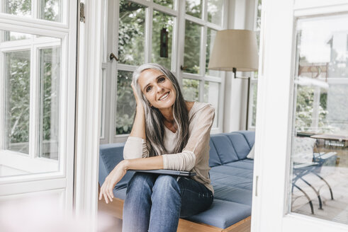 Smiling woman sitting on lounge in winter garden - KNSF000256