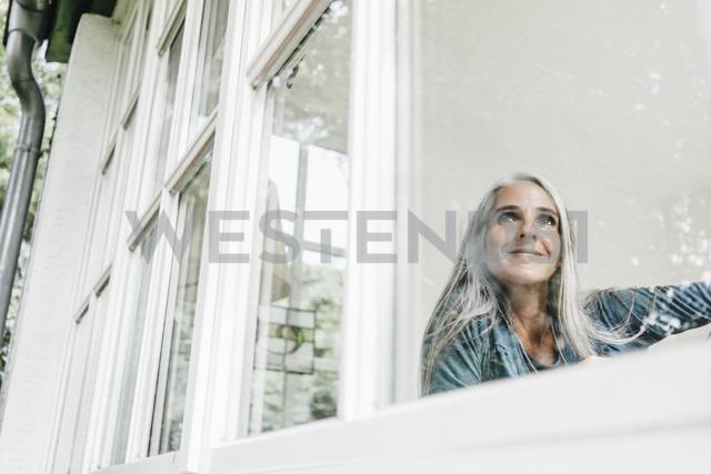Smiling woman at home looking through window - KNSF000268 - Kniel Synnatzschke/Westend61