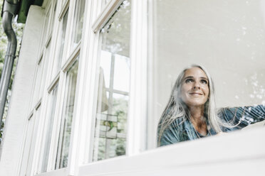 Smiling woman at home looking through window - KNSF000268