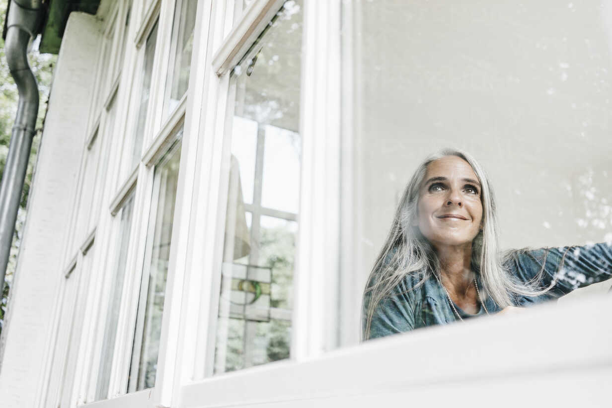 Smiling woman at home looking through window - KNSF000268 - Kniel Synnatzschke/Westend61