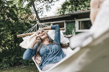 Laughing woman on the phone lying in hammock in the garden - KNSF000280