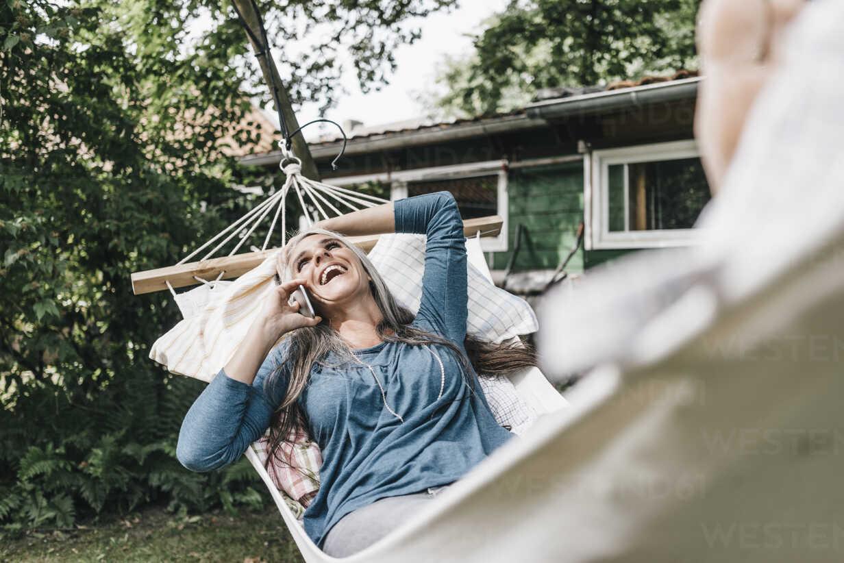 Laughing woman on the phone lying in hammock in the garden - KNSF000280 - Kniel Synnatzschke/Westend61