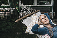 Woman relaxing in hammock in the garden - KNSF000283