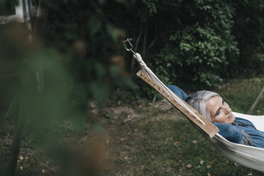 Woman relaxing in hammock in the garden - KNSF000286