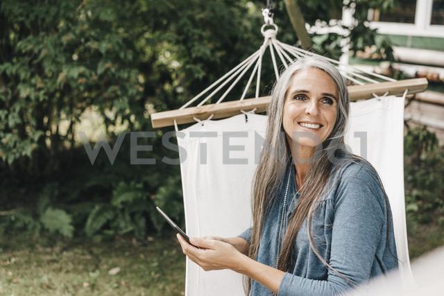Portrait of smiling woman with smartphone sitting in hammock in the garden - KNSF000289 - Kniel Synnatzschke/Westend61