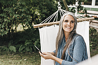 Portrait of smiling woman with smartphone sitting in hammock in the garden - KNSF000289