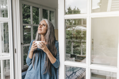 Smiling woman leaning at door frame of her winter garden with cup of coffee looking up - KNSF000292