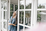 Pensive woman leaning against door case of her winter garden - KNSF000295