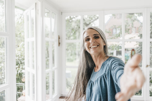 Portrait of smiling woman inviting viewer in her winter garden - KNSF000298