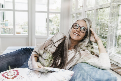 Portrait of smiling woman with e-book lying on lounge in her winter garden - KNSF000301