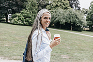 Smiling woman with coffee to go in the park - KNSF000307