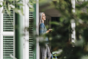 Smiling woman leaning at door frame with cup of coffee at home - KNSF000310