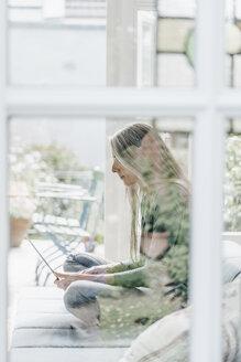 Woman sitting on lounge in winter garden using laptop - KNSF000325