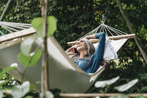 Woman on the phone relaxing in hammock in the garden - KNSF000334