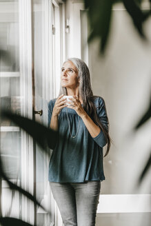 Woman with bowl of coffee looking through window - KNSF000337