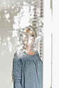 Woman standing behind reflecting windowpane - KNSF000340
