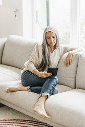 Woman with long grey hair sitting on the couch with e-book - KNSF000343