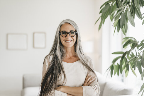 Portrait of smiling woman with long grey hair and spectacles at home - KNSF000346