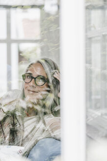 Portrait of smiling woman sitting in winter garten looking through window - KNSF000352