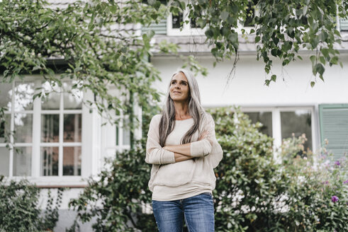 Smiling woman with long grey hair standing in the garden - KNSF000355