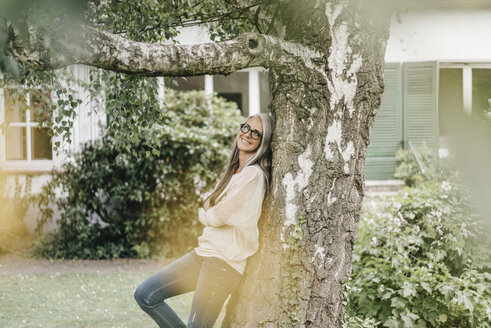 Smiling woman leaning against tree in the garden - KNSF000358