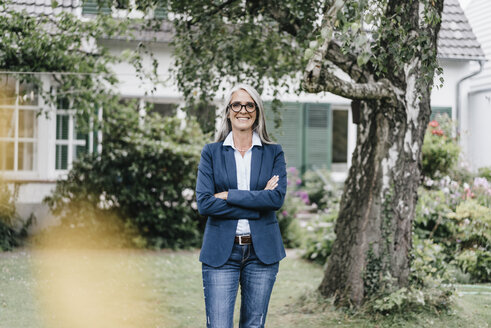 Portrait of smiling businesswoman with long grey hair wearing spectacles standing in the garden - KNSF000361