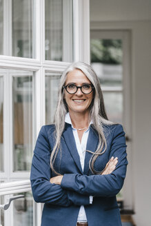 Portrait of smiling businesswoman with long grey hair and spectacles standing in front of open glass door - KNSF000367