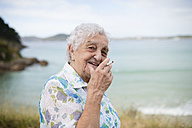 Portrait of smiling senior woman with cigarette - RAEF001416