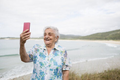 Happy senior woman taking selfie on the beach - RAEF001419