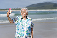Smiling senior woman taking selfie on the beach - RAEF001425
