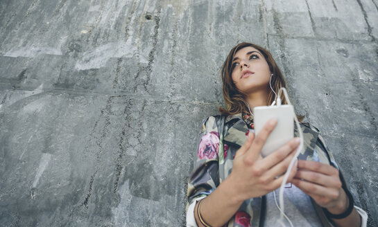 Young woman leaning against concrete wall listening music with earphones - DAPF000281