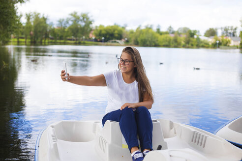 Russia, Tikhvin, teenager girl with smartphone, sitting in boat, selfie - KNTF000468