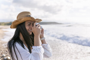 Asturias, Spain, beautiful young woman with a camera on the beach - MGOF002203