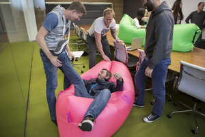 Group of business people playing around with inflatable sofas - ZEF009768