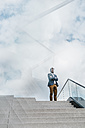 Businessman standing atop of stairs - KNSF000422